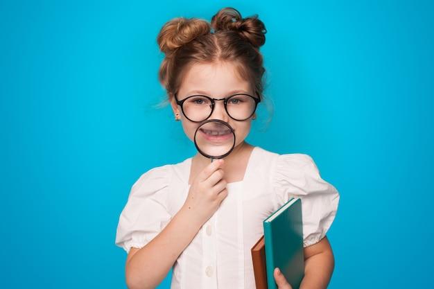 Piccola ragazza caucasica con gli occhiali in possesso di alcuni libri e lente d'ingrandimento sorridente su una parete blu