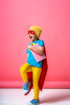 Piccolo bambino allegro che gioca un supereroe con un mantello rosso e una stella, con un libro