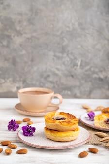Piccole torte di formaggio con marmellata e mandorle con tazza di caffè su un bianco di legno