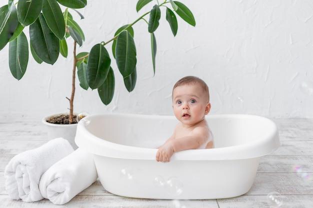 Un bambino di 8 mesi si bagna in un bagno con schiuma e bolle di sapone