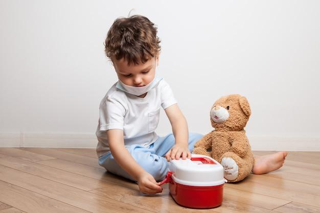 Un bambino piccolo, un ragazzo in maschera medica con uno stetoscopio sul collo, fa il medico con un armadietto dei medicinali per bambini, fa un'iniezione a un orsacchiotto e misura la temperatura