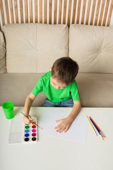 Un bambino piccolo disegna con un pennello e dipinge su carta a un tavolo nella stanza. vista dall'alto