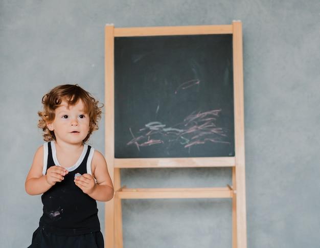 Il bambino piccolo disegna con il gesso sulla lavagna