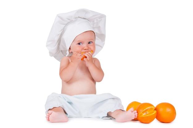 Un bambino piccolo mangia una fetta d'arancia in una tuta da cuoco su un bianco.