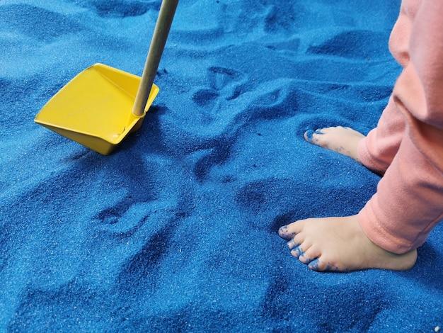 Piccoli piedi del bambino che giocano con la pala in sabbia blu.