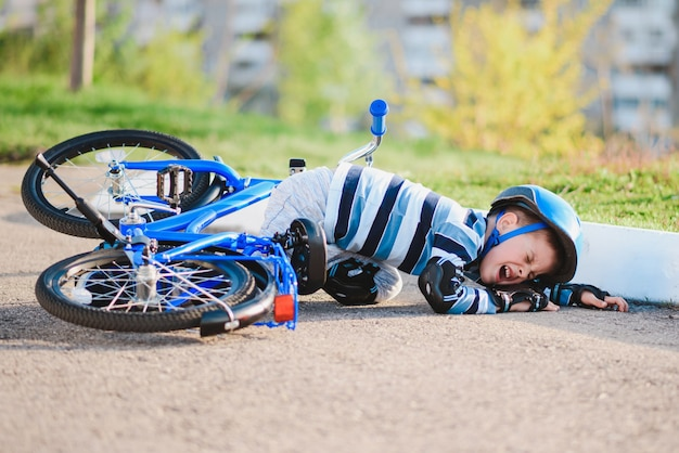Un bambino è caduto da una bicicletta sulla strada, piangendo e urlando di dolore.