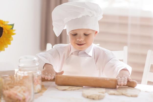 Un bambino piccolo sotto forma di cuoco arrotola la pasta su un tavolo