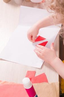 Un bambino piccolo incolla la carta