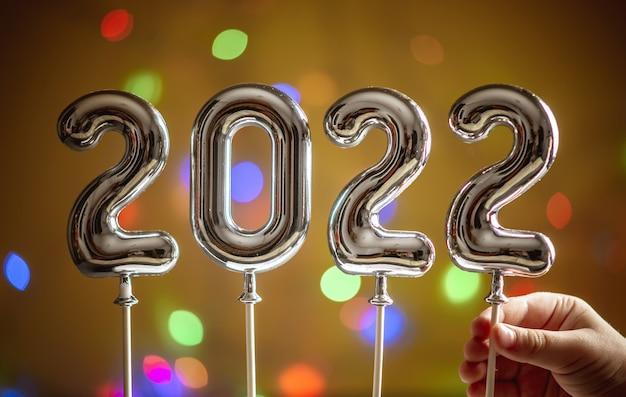 La mano di un bambino piccolo tiene l'ultimo simbolo 2 nel numero 2022 su uno sfondo dorato scuro con un bokeh. concetto di auguri di felice anno nuovo