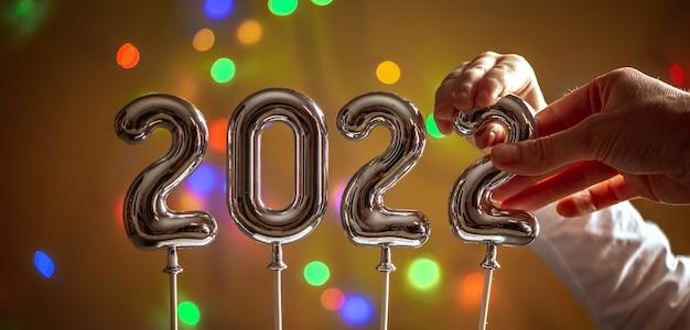 La mano del bambino piccolo e la mano della mamma stanno insieme impostando l'ultimo simbolo 2 nel numero 2022 su uno sfondo dorato con un bokeh. concetto di auguri di buon anno e preparazione per le vacanze