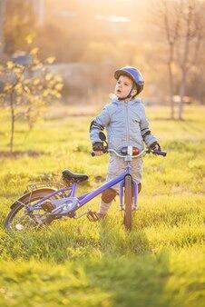 Un bambino piccolo in un casco conduce una bicicletta in una giornata di sole al tramonto