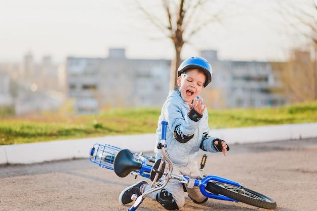 Un bambino piccolo con casco e protezione è caduto da una bicicletta sull'asfalto e non è rimasto ferito