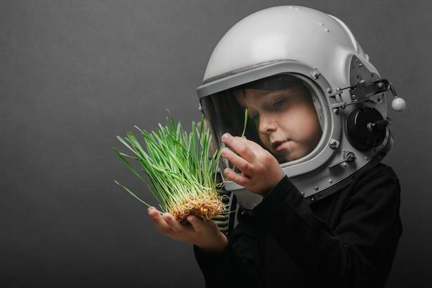 Un bambino piccolo tiene le piante in un casco di aeroplano. il bambino guarda l'erba attraverso il vetro. il concetto di protezione ambientale.