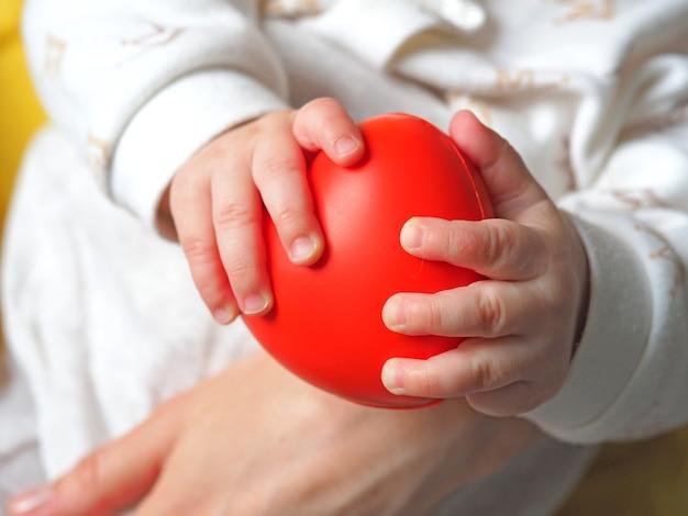 Un bambino piccolo tiene in mano un cuore rosso. concetto di amore materno, salute del bambino