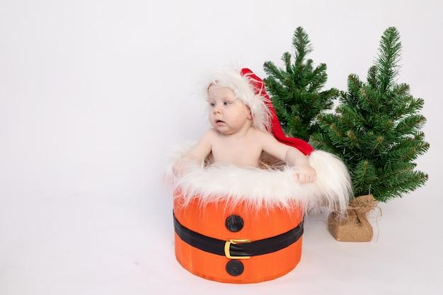 Un bambino piccolo è seduto nel cestino di babbo natale su uno sfondo bianco isolato in un cappello e con alberi di natale, un posto per il testo