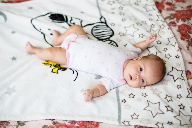 Un bambino piccolo giace su un lenzuolo bianco. vestiti per bambini che giacciono nella culla
