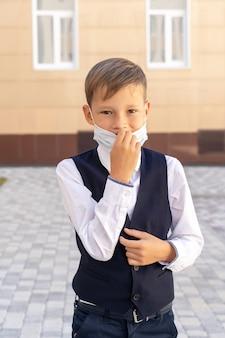 Un bambino piccolo con una maschera durante un'epidemia di virus vicino al muro della scuola