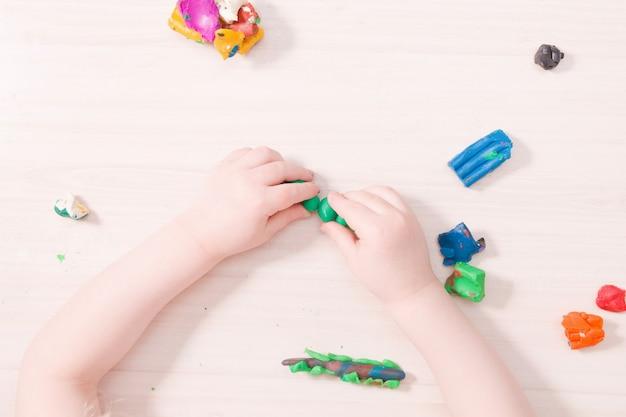 Un bambino piccolo scolpisce un bruco dalla plastilina verde su un tavolo di legno