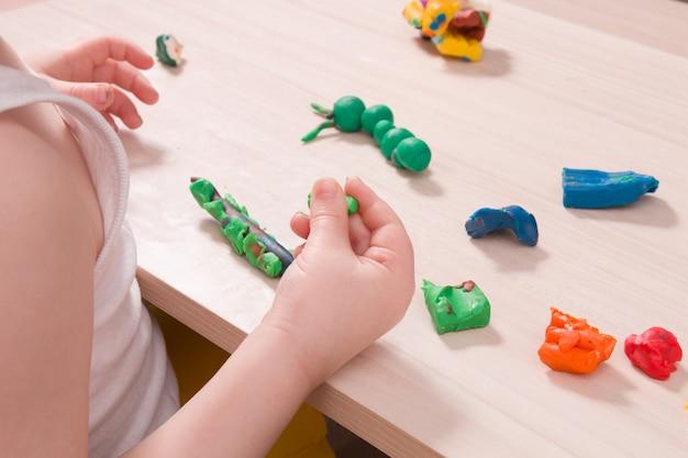 Un bambino piccolo scolpisce dalla plastilina su un tavolo di legno