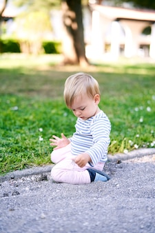 Un bambino piccolo si siede su un prato verde e cosparge la sabbia con la mano
