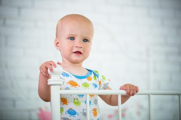 Un bambino piccolo sta in piedi sul letto tenendosi alla testiera