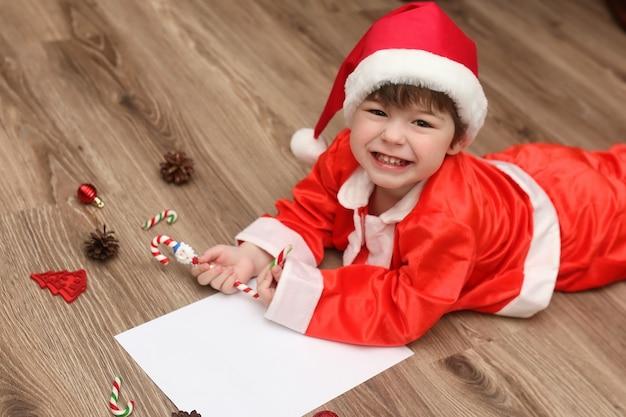 Bambino piccolo vestito da babbo natale che scrive una lettera con gli auguri per il nuovo anno