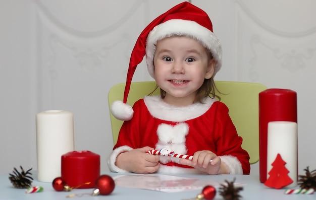Bambino piccolo vestito da babbo natale che scrive una lettera con i desideri