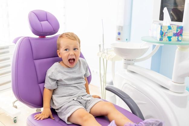 Un bambino piccolo di due anni seduto su una poltrona odontoiatrica lilla con la bocca aperta.