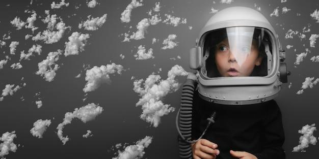 Un bambino piccolo vuole pilotare un aereo indossando un casco aereo che vola tra le nuvole