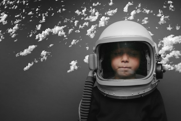 Un bambino piccolo vuole pilotare un aereo indossando un casco da aereo