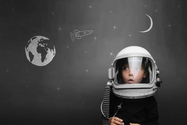 Un bambino piccolo vuole pilotare un aereo che indossa un casco da aeroplano