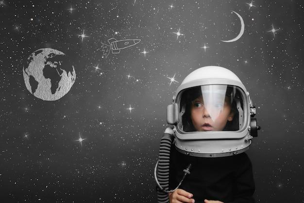 Il bambino piccolo vuole volare nello spazio indossando un elmetto da astronauta