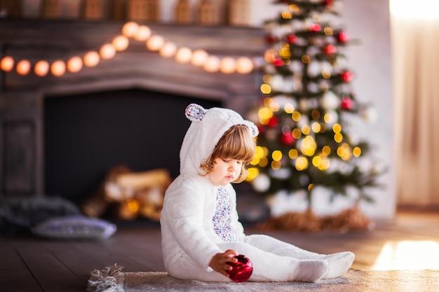 Un bambino piccolo con un costume da coniglio bianco si siede vicino all'albero di natale e tiene una palla di natale rossa. foto di alta qualità