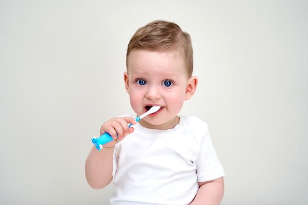 Un bambino piccolo con gli occhi azzurri tiene in mano gli spazzolini da denti.