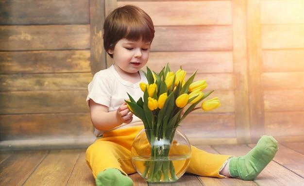 Un bambino piccolo con un mazzo di tulipani gialli. un ragazzo con un dono di fiori in un vaso. un regalo per le ragazze in vacanza femminile con tulipani gialli sul pavimento.