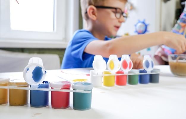 Un bambino piccolo con gli occhiali, che disegna con la vernice. la creatività dei bambini a casa.