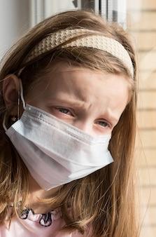 Piccolo bambino con maschera chirurgica guardando fuori dalla finestra