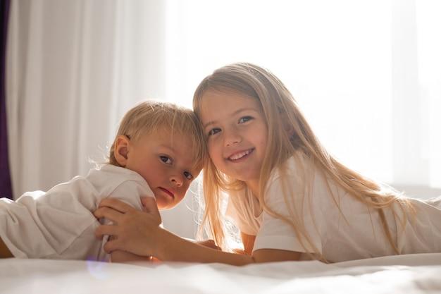 I bambini piccoli fratello e sorella in magliette bianche sono sdraiati sul letto e si guardano l'un l'altro