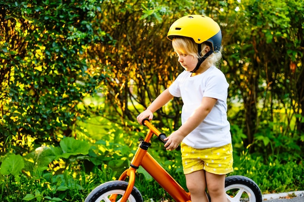 Bambina piccola con caschi e bici da equilibrio che giocano all'aperto