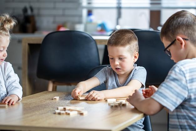 I bambini piccoli giocano a un gioco da tavolo con cubi di legno a casa in cucina.