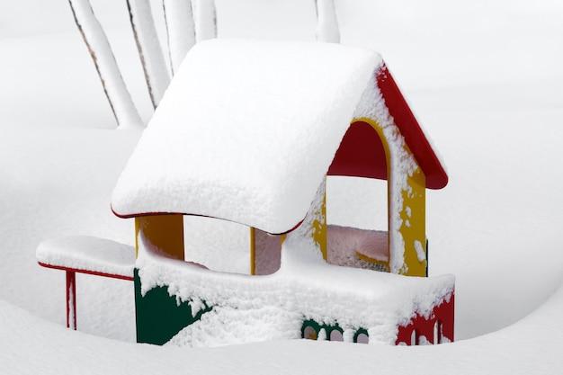 Piccola casa rossogialloverde per bambini nell'asilo per bambini nel paesaggio invernale dopo la nevicata...