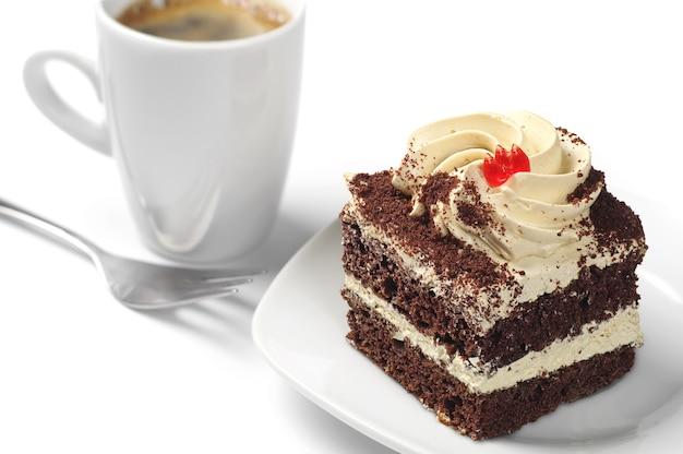 Piccola torta al cioccolato e tazza di caffè su sfondo bianco