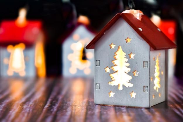 Piccole case di natale con finestre ad albero di natale che brillano dall'interno. case con illuminate