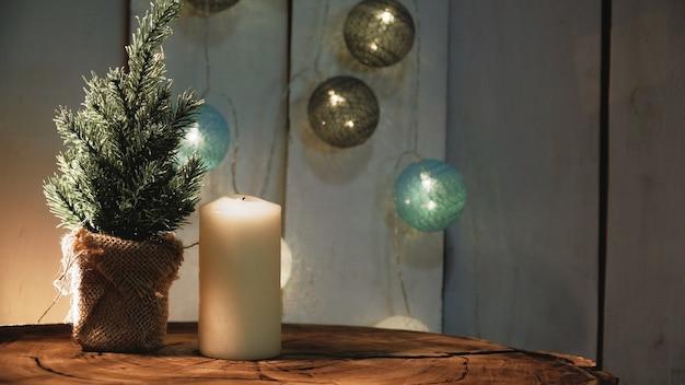 Piccolo albero di natale e candele su una superficie di legno
