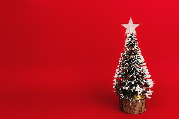 Piccolo albero di natale con stella su sfondo rosso.