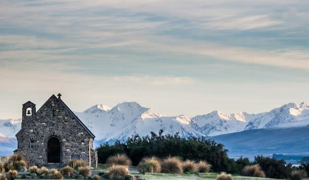 Piccola chiesa con sfondo di montagna girato durante l'alba al lago tekapo, nuova zelanda