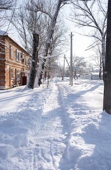 Piccola città ricoperta di neve. piccoli edifici e case in inverno con molti cumuli di neve su una strada.