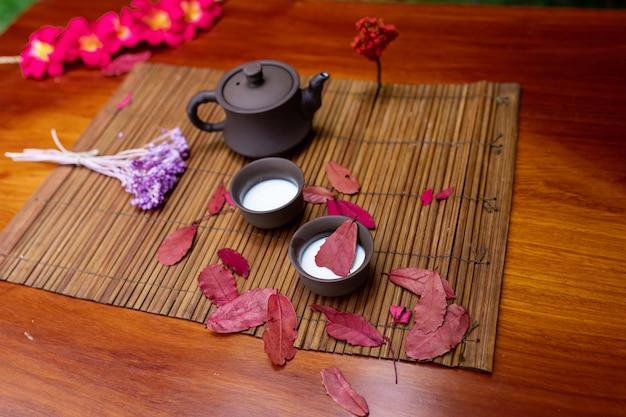 Una piccola teiera di argilla con due tazze per bevande in piedi su una stuoia tra fogli rossi con un rametto di legno di lavanda e fiori di magnolia rossa