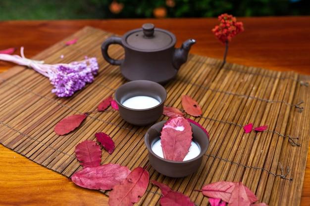Una piccola teiera di argilla con due tazze di latte versato in piedi su una stuoia tra le foglie rosse degli alberi e un rametto di lavanda