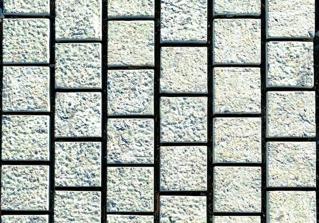 Piccolo marciapiede in ciottoli fatto di pietre cubiche - tessitura piastrellabile, grigio sul marciapiede